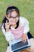Hermosa chica con un ordenador portátil en la hierba — Foto de Stock