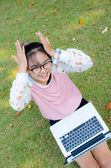 Cute girl is happy with notebook on grass — Stock Photo
