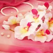 Cute white orchids, necklace and beads on a soft pink background — Stock Photo