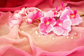 Pink orchids, necklace, beads on a soft pink background — Stock Photo