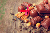 Chocolate candies, cinnamon and nuts — Stock Photo