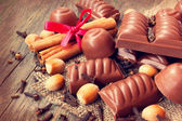 Chocolate candies, cinnamon, nuts — Stock Photo