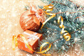Golden ball, gift box and christmas tree branches — Stock Photo