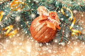 Beautiful golden ball and christmas tree branches — Stock Photo
