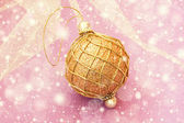 Golden christmas ball on a pale pink background — Stock Photo