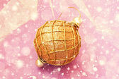 Golden shiny christmas ball on a pale pink background — Foto Stock
