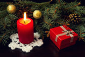 Red candle, christmas gifts and decorations — Stock Photo