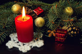 Red candle and christmas gifts — Stock Photo