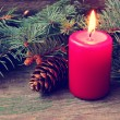 Red christmas candle and pine tree branches — Zdjęcie stockowe