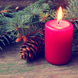 Red christmas candle and pine tree branches — Stock Photo
