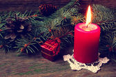 Red candle on a knitted napkin — Stock Photo