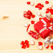 Cute red gift box, ribbons, valentine's hearts on a wooden background — Stock Photo #36886779