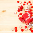 Red gift box, ribbons, valentine's hearts on a wooden background — Stock Photo