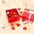 Open red gift box with small hearts — Stock Photo
