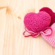 Knitted toys in the shape of hearts on a wooden background — Stock Photo #37378513