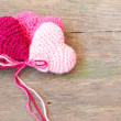 Knitted toys in the shape of hearts on an old wooden background — Stock Photo #37763741
