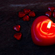 Stock Photo: Candle in the shape of heart on an old scratched wooden background