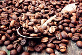 Coffee beans in a spoon on wooden background — Stock Photo