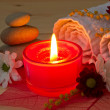 Burning red aroma candle close up and spa stuff — Stock Photo #44765831