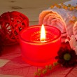 Red aroma candle close up and spa stuff — Stock Photo #44765847