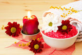 Burning aroma candle, spa salts and flowers — Stock Photo