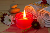 Burning red aroma candle close up and spa stuff — ストック写真