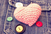 Cute pink knitted heart on a jeans pocket — Stock Photo