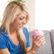 Cute blond Caucasian woman holding piggy bank — Stok fotoğraf