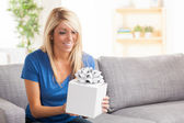 Attractive white female holding gift with bow — Stock Photo