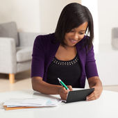 Cute young black female doing finances — Zdjęcie stockowe