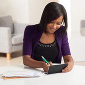 Mignonne jeune femelle noire faisant des finances — Photo