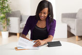 Cute young black female doing finances — Stok fotoğraf