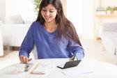 Cute Hispanic female paying bills — Stock Photo