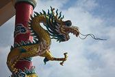 Golden chinesischer drache, um rote stange und hellen himmel gewickelt — Stockfoto