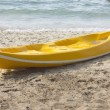 Stock Photo: Single yellow kayak on the beach.