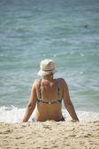 Donna seduta sulla spiaggia e guardare il mare — Foto Stock
