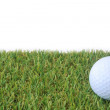 Isolated golf ball on green grass over white background — Stock Photo