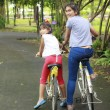 Woman and young girl on bikes outdoors smiling — Stock Photo #47862137