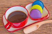 Red cup of coffee and colorful Biscuit on wooden table backgroun — Stock Photo
