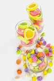 Colorful candy in glass saucer and bowl isolated on white backgr — Stock Photo