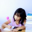 Portrait of cheerful Asian young girl doing her homework — Stock Photo #51313705