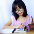 Portrait of cheerful Asian young girl doing her homework — Stock Photo #51313715