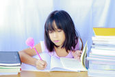 Portrait of cheerful Asian young girl doing her homework  — Stock Photo