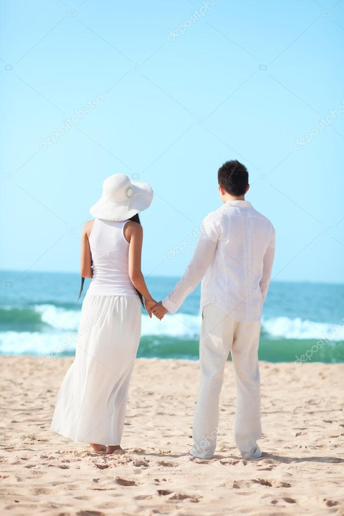 Young couple standing together on the beach   Stock Photo #12482640