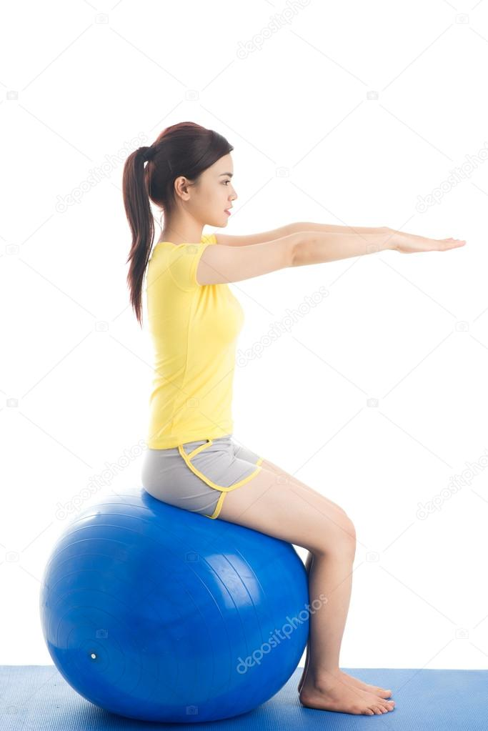Girl keeping balance sitting on exercise ball, isolated against white background — Stock Photo #14634115