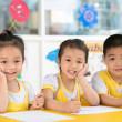 niño y niñas sentados en el jardín de la infancia — Foto de Stock