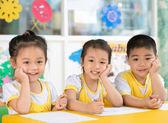 Boy and girls sitting in the kindergarten — Stock Photo