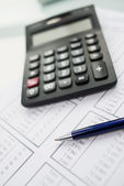 Calculator and pen on the table — Stock Photo
