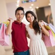 Young couple standing and smiling with bags in hands — Stock Photo