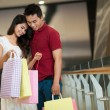 Asian man and woman standing and looking in a shopping bag — Foto de Stock